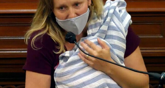 Une mère masquée un enfant dans ses bras prononçant  un discours passionné à l' Assemblée de l'État de Californie. ( Publié le 02/10/2020.)